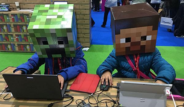 Dos niños, uno con cabeza de Creeper y otro con cabeza de Steve, prueban Minecraft Education Edition durante la MineCon 2016.