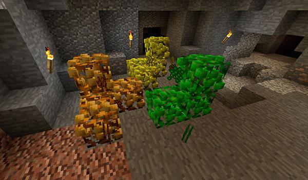 Imagen donde podemos ver como un personaje encuentra arbustos minerales, del mod Ore Shrubs 1.12, 1.12.1 y 1.12.2, en el interior de una cueva en Minecraft.