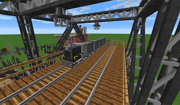 Imagen donde podemos ver una locomotora, junto a varios vagones, circulando por un puente metálico, creado con los bloques y objetos del mod Industrial Renewal 1.12.2.