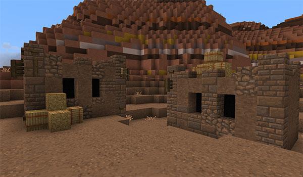 Imagen donde podemos ver dos pequeñas construcciones, en el bioma de Mesa, utilizando las texturas de A Little Taste of Jerm Texture Pack 1.16, 1.15 y 1.12.