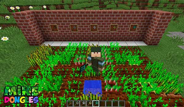 Imagen donde vemos a un jugador trabajando en su huerto de Minecraft, haciendo uso de algunas de las herramientas que añade el mod Mike Dongles 1.12.2.
