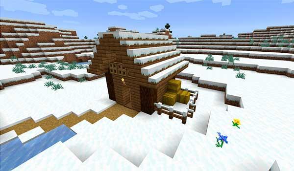 Imagen donde podemos ver un paisaje, con una casa cubierta de nieve, con el mod Snow Real Magic 1.16.1 y 1.16.2 instalado.